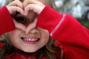 تصنع من يديها شكل قلب الحب وتنظر من داخله بعينها بصورة لفاتة رائعة ترتدي الأحمر